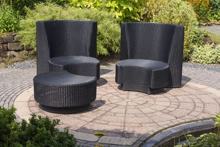 teracce with rattan relax chairs in garden with small pond in front and green plants as background