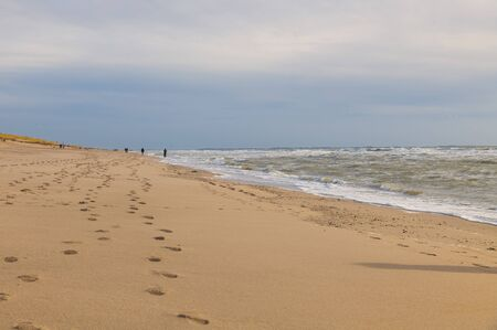 people walking at the beach at the northsea beach with hard wind and waves with dark clouds and sky