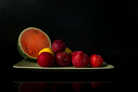 still life with a green bowl on a reflective background with lemons, plums and half a water meleon