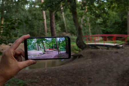woman making a photo with smartphone of the typical red japanese bridge in garden with forest trees and plants and sand at the border of small water.