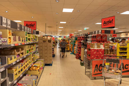 Weert,Holland,05-sep-2020: woman shopping in a supermarket with shells full of food and non food sale products