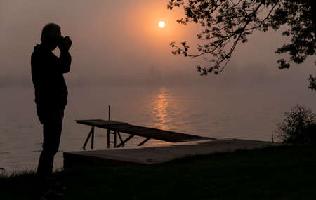 silhouette photographer at wooden jetty during sunset in the early morning over the river maas in limburg in holland with the trees mist and hazy fog Banco de Imagens