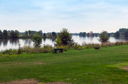 the river maas in holland with bench and fireplace at the border of the water, the maas is a river for watersport but also for water transport