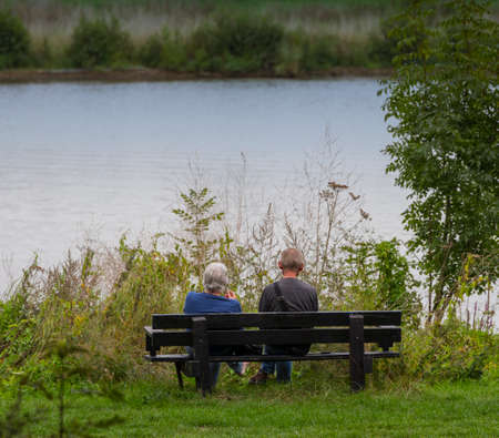 Maashees,Holland,09-sep-2020:older couple sit on a bench looking out over the river mesh and think about life Editorial