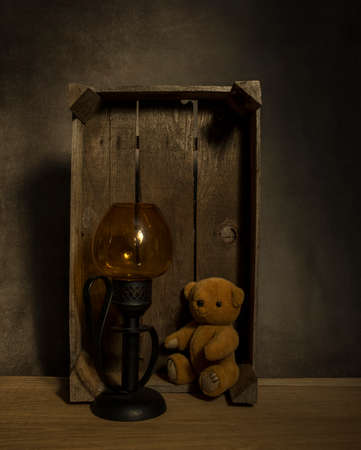 still life with old teddy bear and a golden light in an old wooden box on a table with dark background