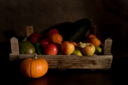 a still life of fruit in an old wooden box with a brown and black mixed background Banco de Imagens