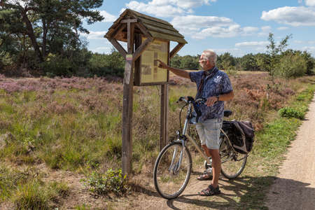 Bergen,holland,10-sep-2020:man on an ebike is looking for information about the Maasduinen nature reserve in Limburg