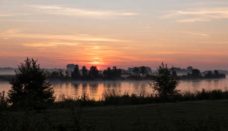 sunrise in the early morning over the river maas in limburg in holland with the trees mist and hazy fog
