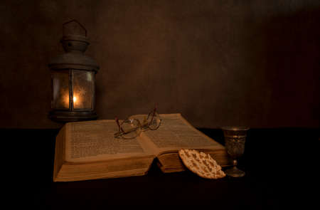 a still life of a bible with an old pewter lamp with a tea light burning with an old bible and supper