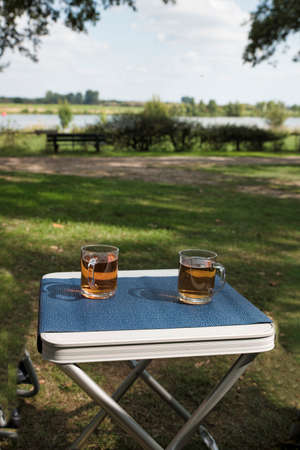 two glasses of tea during afternoon break outside on a table on the river Maas Banco de Imagens