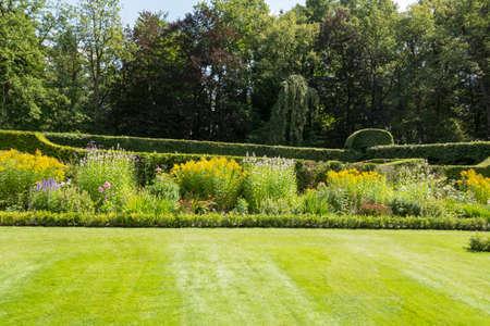 landscape garden with borders full flowers Foto de archivo