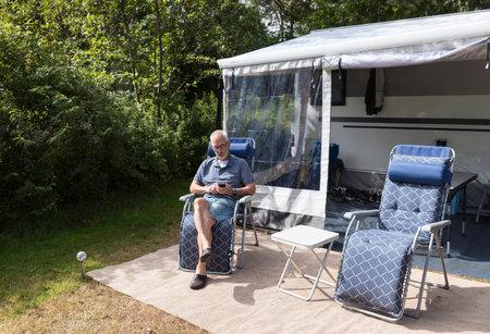 man sitting in front of caravan