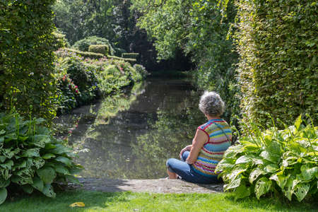 mature woman sitting at a lake during summer