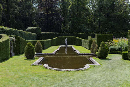 park with hedges of conifers and boxwood with a pond with a statue behind it
