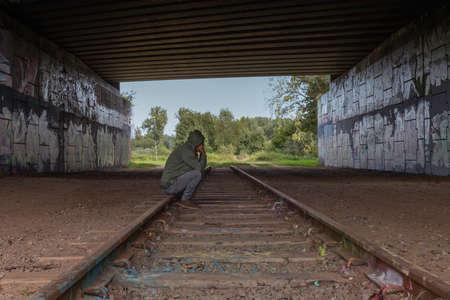 man sitting on a railway track