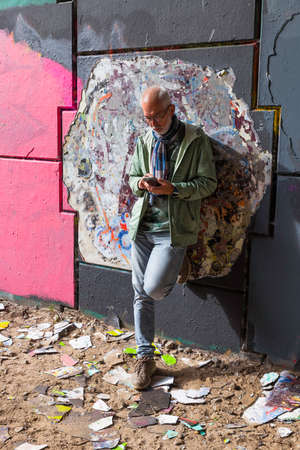 a wall full with graffiti and a man busy with his cellphone Foto de archivo