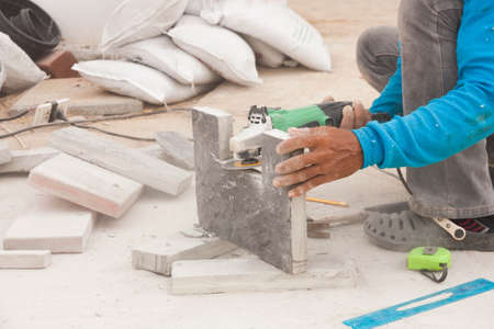 Construction worker is cutting grey pavement tile