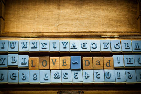 love dad spelling with rubber stamp in wood box photo