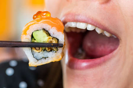 Woman mouth eat sushi photo