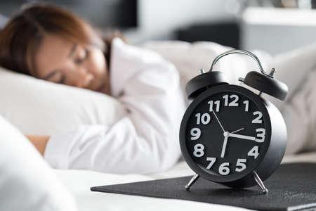 Asiatische Frau, die auf Bett schläft und aufwachen mit Wecker