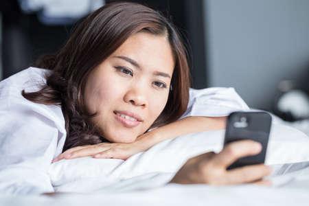 asian women: Young happy asian woman using smartphone Stock Photo