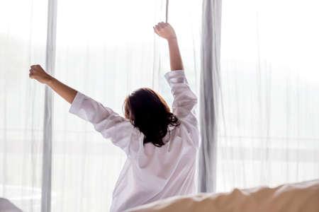 Junge asiatische Frau, die sich in den Morgen