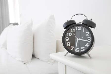 블랙 알람 시계와 침대