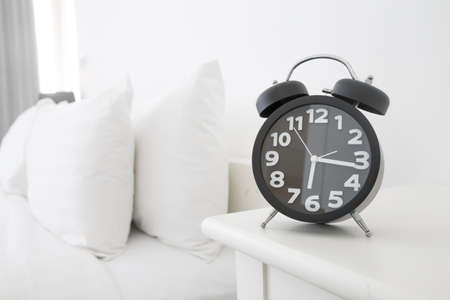 Black alarm clock and bed Stock Photo