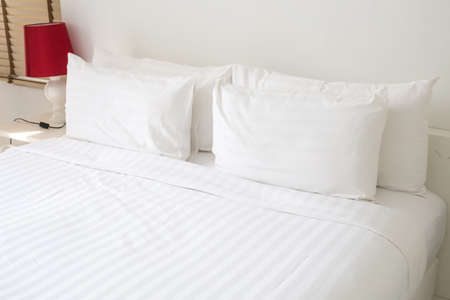 bed sheet: White bed sheets and pillows Stock Photo