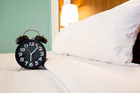 bed time: Black alarm clock and bed Stock Photo
