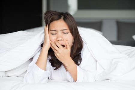 cansancio: Sleepy mujer asiática que bosteza en cama en su casa