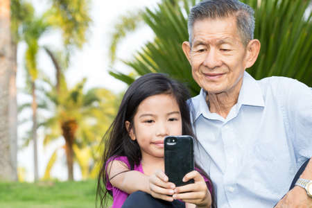 old asian: Grandfather and grandchild making selfie with smart phone in the park Stock Photo