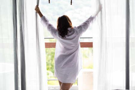 Asiatische Frauen öffnen den Vorhang