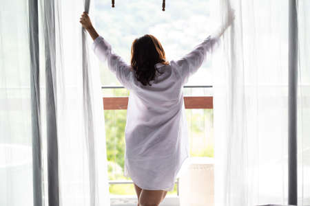 ventana abierta interior: Las mujeres asi�ticas abren la cortina Foto de archivo