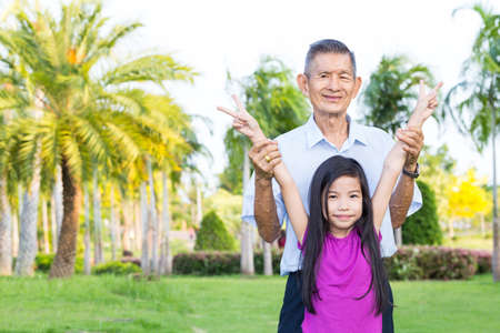 life insurance: Grandfather and grandchild have fun and play in park
