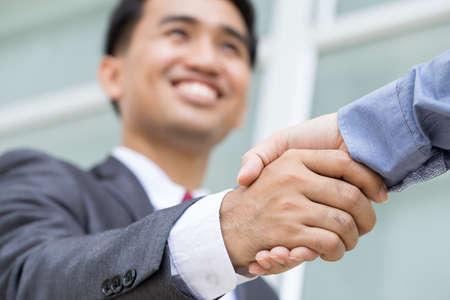 saludo de manos: Asia apret�n de manos la toma de hombre de negocios con la cara sonriente