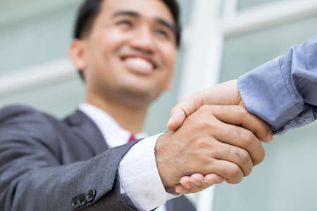 Asian businessman making handshake with smiling face