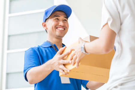 delivery package: Woman accepting a delivery of cardboard boxes from deliveryman