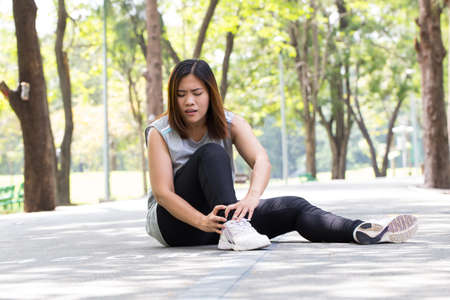 Sports injury. Woman with pain in ankle while jogging 写真素材