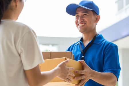 deliveryman: Woman accepting a delivery of cardboard boxes from deliveryman