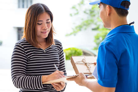 courier man: Asian woman signing receipt of delivered package