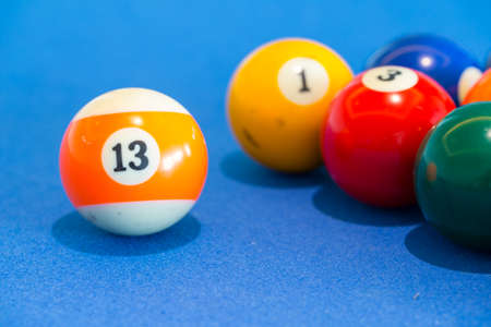 snooker tables: orange snooker ball with number thirteen on it with other colorful balls placed in a row on a table