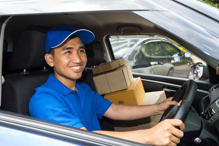 courier man: Delivery driver driving with parcels on seat Stock Photo