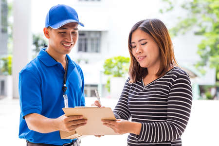 delivery service: Asian woman signing receipt of delivered package