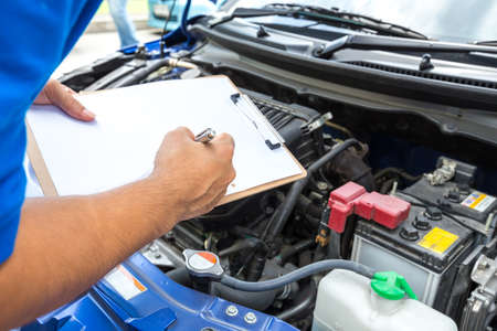 mecanico automotriz: hombre mecánico con portapapeles y comprobar el coche Foto de archivo