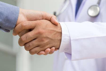paciente: El doctor da la mano a un paciente