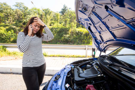 breaking down: Asian women calling for assistance after breaking down car engine