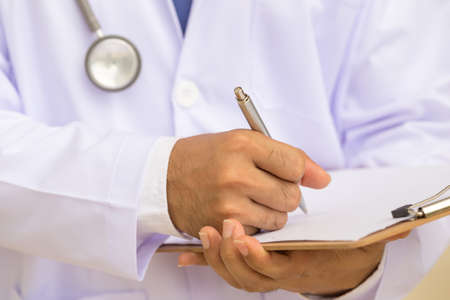 doctor writing: Doctor writing on clipboard Stock Photo