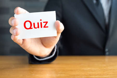 quiz test: Quiz, message on white card and hold by  businessman
