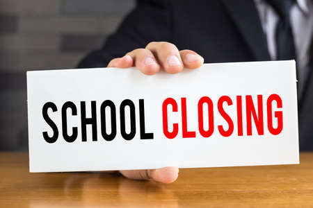 closing: School closing, message on white card and hold by  businessman